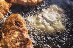Fritters τηγανητά στο τηγάνισμα του τηγανιού Στοκ Φωτογραφίες