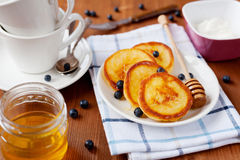 Fritters of cottage cheese with honey, sour cream and bilberry or blueberry on a white plate Royalty Free Stock Photos