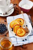 Fritters of cottage cheese with honey, sour cream and bilberry or blueberry on a white plate Stock Photography