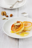 Fritters of cottage cheese on a white plate. Fritters of cottage cheese with honey and nuts on a white plate Royalty Free Stock Photo
