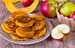 Fritters met pompoen en appelen op een beige plaat Stock Afbeeldingen