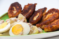 Fritters of potatoes with potato salad and boiled eggs Royalty Free Stock Images