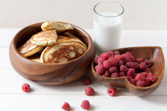 Fritters with a raspberry on wooden plate. Fritters with a raspberry and milk on wooden plate Royalty Free Stock Photo