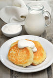 Fritters with sour cream and milk jug Stock Photo