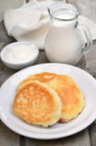Fritters, sour cream and milk jug Royalty Free Stock Photography