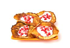 Fritters on a white background on a plate. Pancakes on an orange plate with sour cream, jam and pomegranate Stock Photo