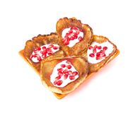 Fritters on a white background on a plate. Pancakes on an orange plate with sour cream, jam and pomegranate Stock Images