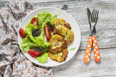 Fritters of zucchini and fresh vegetable salad Stock Photos