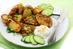 Fritters zucchini, potatoes and sour cream sauce. Royalty Free Stock Image