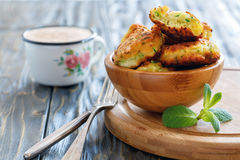Fritters of zucchini in a wooden bowl. Fritters of zucchini in bowl on wooden kitchen table Royalty Free Stock Photography