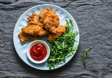 Frittiertes Brot zerkrümelt gebratenes Hühnerleiste mit Ketschup und Salat - köstlicher Aperitif, Tapas auf grauem Hintergrund stockfotos