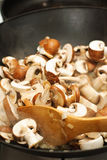 Frittura dei funghi in un wok Immagini Stock