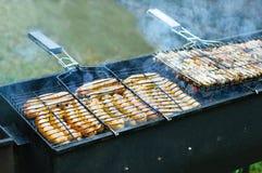 Frittura del barbecue delle salsiccie sulla griglia fotografia stock