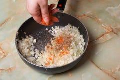 Frittura della cipolla. Aggiunga il pepe rosso. Fotografia Stock