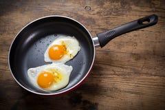 Frittura delle uova in pentola sulla tavola Immagine Stock