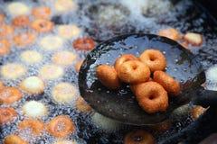 Frittura nel grasso bollente del vada di medu nella pentola Medu Vada è uno spuntino saporito dall'India del sud, alimento molto  fotografia stock