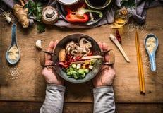 Frittura vegetariana di scalpore che cucina preparazione Le mani femminili delle donne che tengono poco vaso del wok con le verdu immagini stock libere da diritti