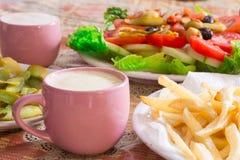 Fritture colorate del frensh e dell'insalata con il cetriolo marinato sui piatti bianchi Immagini Stock Libere da Diritti