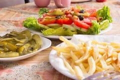 Fritture colorate del frensh e dell'insalata con il cetriolo marinato sui piatti bianchi Immagine Stock