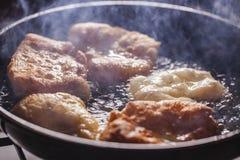 Friture de beignets sur la poêle Photographie stock libre de droits