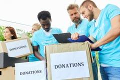 Frivilliga volontärer med donationaskar fotografering för bildbyråer