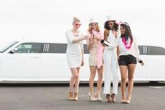 Frivola kvinnor som dricker champagne bredvid en limousine Royaltyfria Bilder
