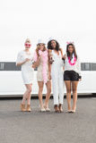 Frivola kvinnor som dricker champagne bredvid en limousine Arkivfoton