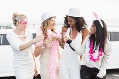 Frivola kvinnor som dricker champagne bredvid en limousine Fotografering för Bildbyråer