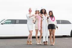 Frivola kvinnor som dricker champagne bredvid en limousine Royaltyfri Foto