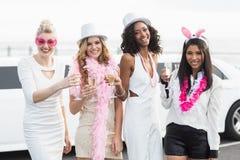 Frivola kvinnor som dricker champagne bredvid en limousine Royaltyfri Fotografi