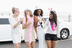 Frivola kvinnor som dricker champagne bredvid en limousine Arkivfoto