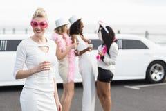 Frivola kvinnor som dricker champagne bredvid en limousine Arkivbilder