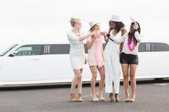 Frivola kvinnor som dricker champagne bredvid en limousine Arkivbild