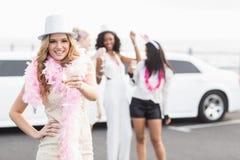 Frivola kvinnor som dricker champagne bredvid en limousine Royaltyfri Bild