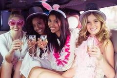 Frivola kvinnor som dricker champagne i en limousine Royaltyfria Bilder