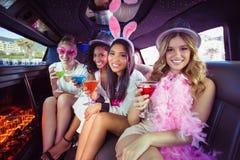Frivola kvinnor som dricker coctailar i en limousine Arkivbilder