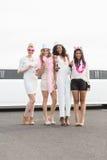 Frivolous women drinking champagne next to a limousine Stock Photos