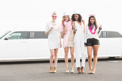 Frivolous women drinking champagne next to a limousine Stock Photography