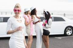 Frivolous women drinking champagne next to a limousine Stock Images