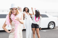Frivolous women drinking champagne next to a limousine Royalty Free Stock Image