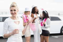Frivolous women drinking champagne next to a limousine Stock Photo
