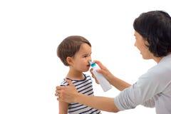 Förälderns hand av en flicka applicerar en isolerad nasal sprej Arkivbild