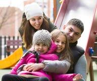 Föräldrar med två döttrar som spelar på children& x27; s-glidbana Arkivfoton