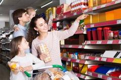 Föräldrar med två ungar som väljer kex i lager Arkivfoto