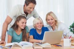 Föräldrar och barn som använder en dator Arkivbild