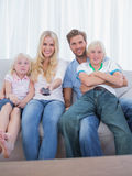 Föräldrar och barn som håller ögonen på TV Fotografering för Bildbyråer