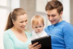 Föräldrar och förtjusande behandla som ett barn med minnestavlaPC Royaltyfria Foton
