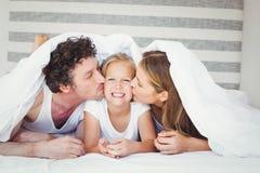Föräldrar som kysser dottern som täckas med duntäcket Arkivfoto