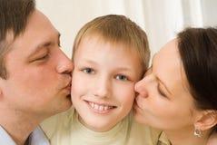Föräldrar som kysser henne barn Royaltyfri Bild