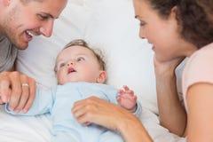 Föräldrar som ser, behandla som ett barn pojken i säng Arkivbild